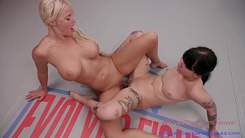 The Blonde Dominates The Brunette In The Ring And He Fucks Her With A Strap-On Dildo